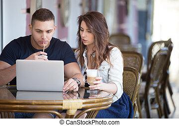 pareja, trabajando, con, computador portatil, en, un, café
