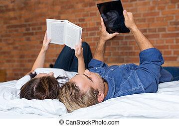 parejas, mentira en cama, con, libro, y, tableta
