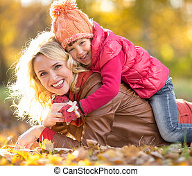 Parent and child lying together on falling leaves. Family outdoor in autumn park. Happy kid is on mother's back.