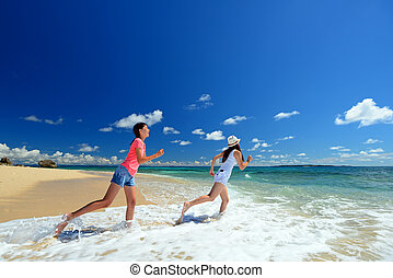 Parent and child running on the beach