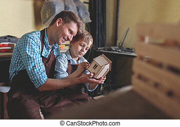 Parent and child with a wooden house
