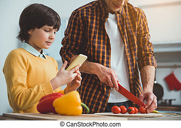 Parent and kid cooking according to online recipe