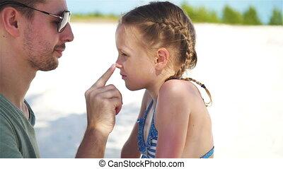 Parent applying sun cream to kid nose. Portrait of cute girl in suncream