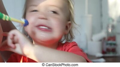 Parent brushes his baby teeth in the bathroom