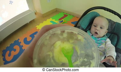Parent feed newborn baby with spoon and potato mash in it. 4K