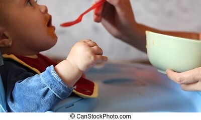 Parent Feeds Children - Little baby is fed by parent with...