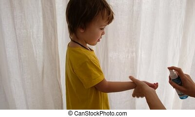 Parent sprays boys hands with a sanitizer house on a white background