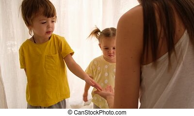 Parent sprays children's hands with a sanitizer house on a white background