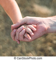 parent holds the hand of a small child. Father holds the child by the hand. close-up. In the background. Support on the way.