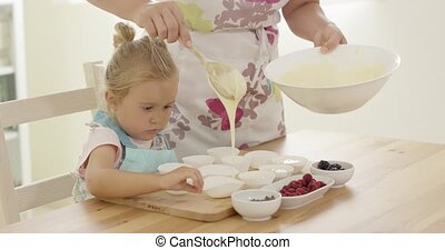 Parent pouring muffin batter into holders