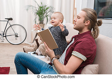 parent reading book to happy daughter at home