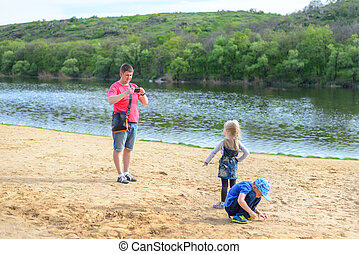 Parent takes photos of children on the beach