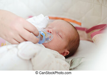 parenting - mother giving dummy to newborn