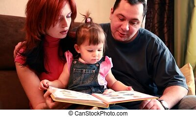 Parents and baby girl are sitting on the sofa considering book