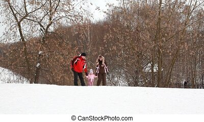 Parents and baby girl are walking in winter