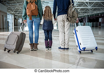 Parents and child holding cases after plane landing - Low ...