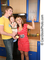 parents and child on hands in kitchen