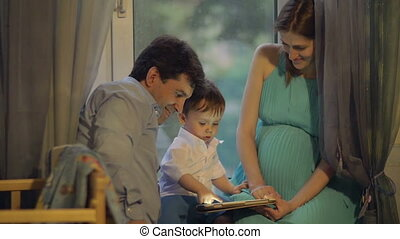 Parents and child playing on touch pad at home