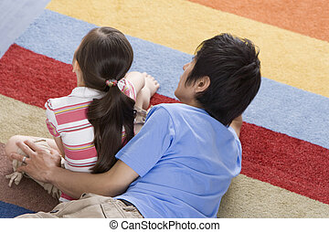 parents and child relaxing on carpet