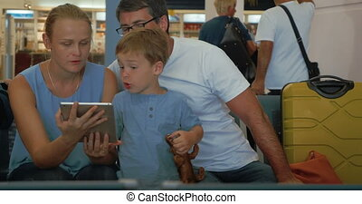 Parents and child using digital tablet at the airport