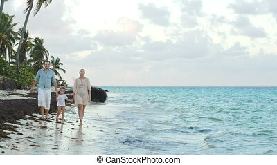 Parents and child walking along the beach holding hands