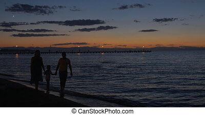 Parents and child walking by the sea in dusk