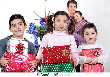 Kids kissing their parents at christmas.