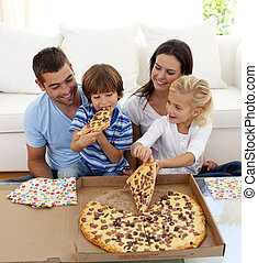 Parents and children eating pizza in living-room all ...