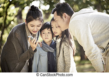 parents and children looking at cellphone together