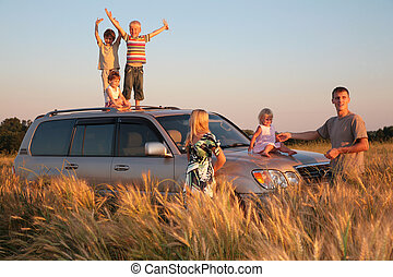Parents and children on offroad car in wheat field