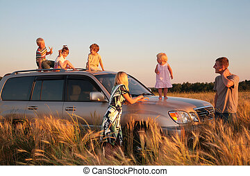 Parents and children on offroad car on wheat field
