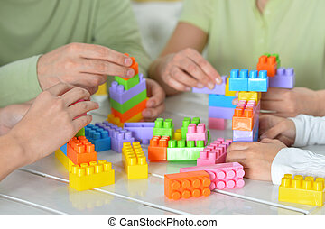 Parents and children playing with colorful plastic blocks
