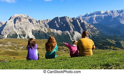 parents and children sitting on a grass and looking at the...