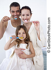 Parents and daughter cleaning their teeth in bathroom -...