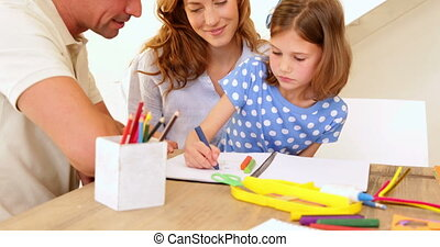 Parents and daughter colouring together at the table at home in living room