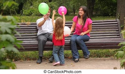parents and daughter play game with balloons in park