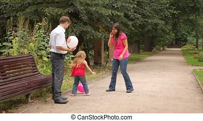 Two parents and their daughter play some game with balloons near bench