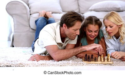 Parents and daughter playing chess