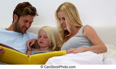Parents and daughter reading book t