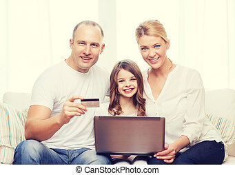 parents and girl with laptop and credit card