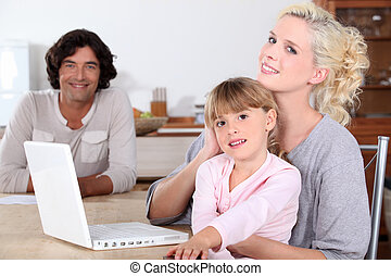 parents and her daughter smiling in the kitchen, a computer is on the table