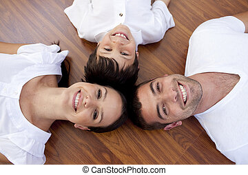 Parents and kid lying on floor with heads together