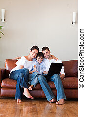 Parents and kid using a laptop with thumbs up and copy-space...