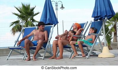 Parents and kids are sitting in deckchairs, and talking