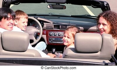 Parents and kids sit in cabriolet and look backward then turn