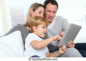 Parents and little boy using electronic tab
