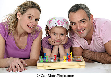 Parents and little girl playing chess together