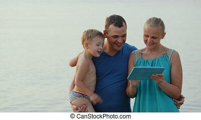 Parents and little son with pad by the sea
