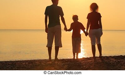 Parents and son are standing on beach