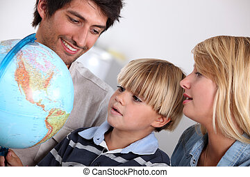 Parents and son looking at a globe
